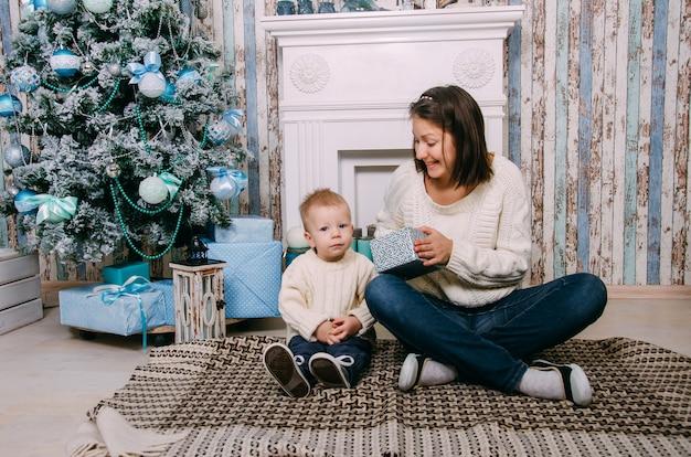 母は小さな男の子に贈り物をします。メリークリスマス、そしてハッピーニューイヤー。