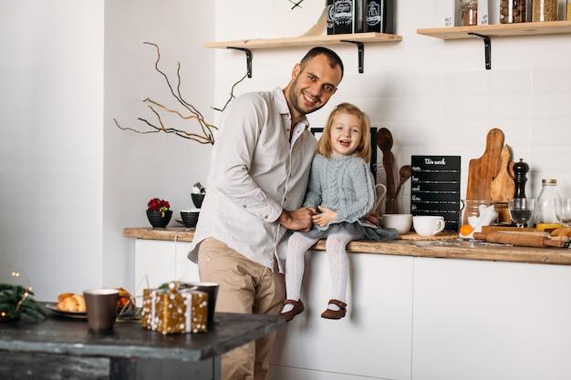 Усмехаясь отец и дочь в кухне дома.