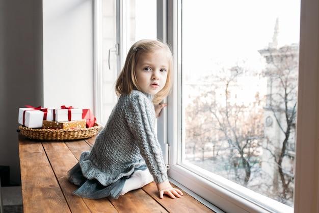 愛らしい少女は窓の近くに座っています。