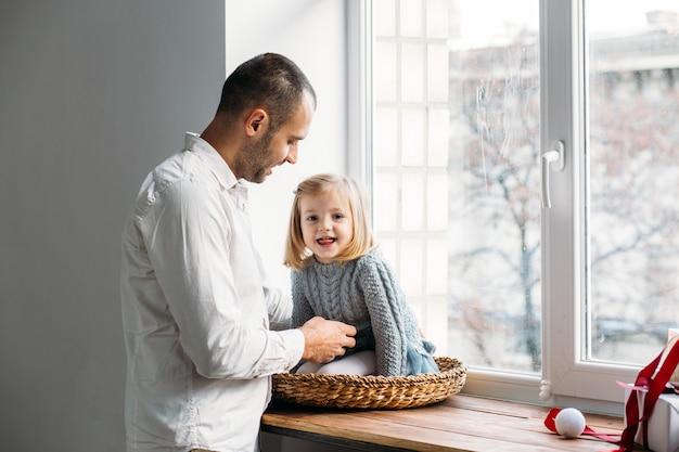 家族と団結のコンセプト。父と娘が窓の近くで遊んでいます。家族の概念。