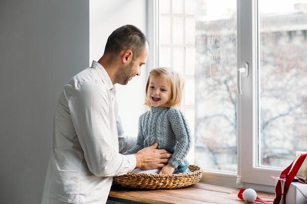 Семья играет возле окна. концепция семьи