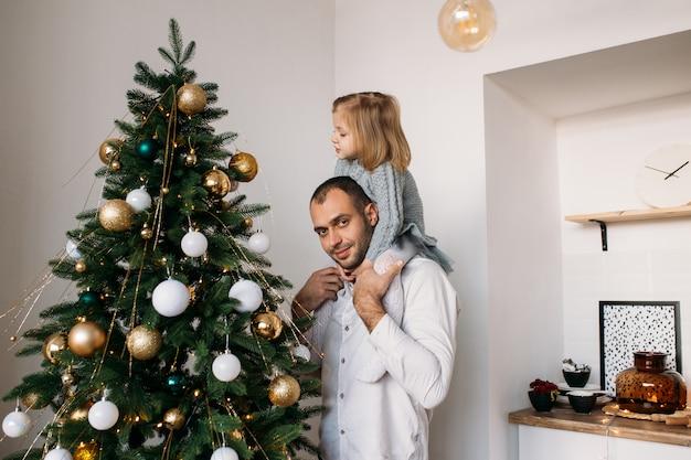 自宅でクリスマスにクリスマスツリーの近くに自宅で娘と父