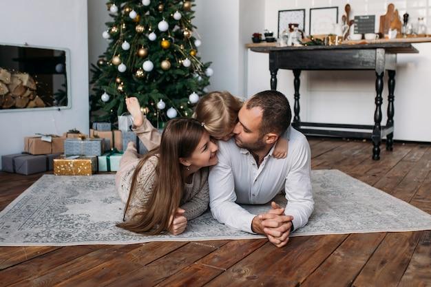 Счастливая семья дома возле елки и рождественские подарки