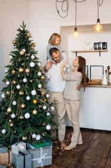 クリスマスツリーとクリスマスプレゼントの近くに家で家族。メリークリスマス、そしてハッピーニューイヤー!