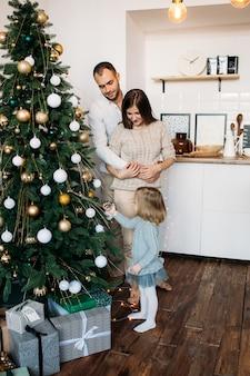 両親と小さな娘が自宅のクリスマスツリーを飾る。メリークリスマス、そしてハッピーニューイヤー!