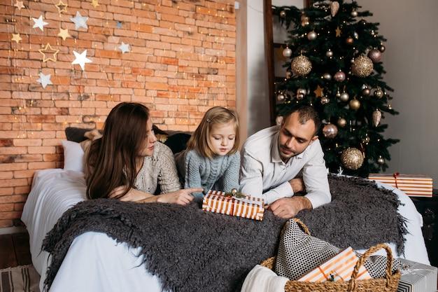 メリークリスマスとハッピーホリデー!陽気な親と自宅のベッドで贈り物を交換するかわいい娘の女の子。