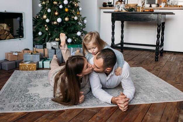 両親と自宅のクリスマスツリーの近くの床にプレゼントと笑い。クリスマスの朝。