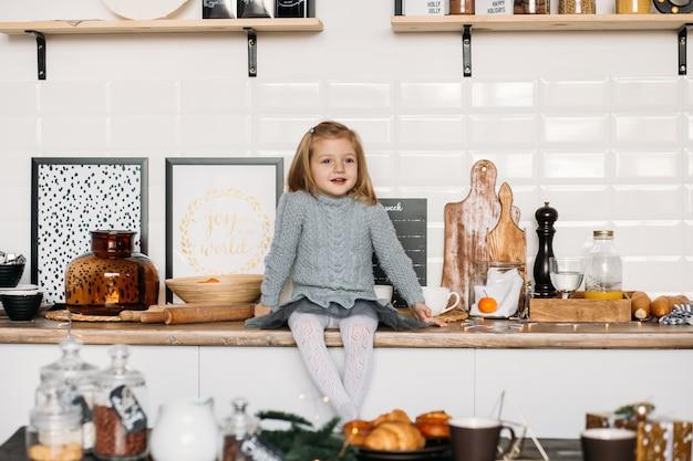 微笑んでいる女の子は台所のテーブルに座っています。クリスマスの朝