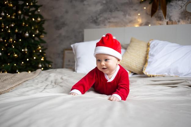サンタの赤ちゃん。赤いクリスマスキャップを着て、ベッドの上のかわいい子