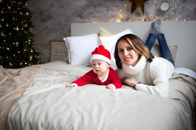 母親と赤ちゃんのクリスマス休暇に自宅のベッドに