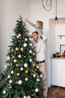 自宅のクリスマスにクリスマスツリーの近くの娘と父
