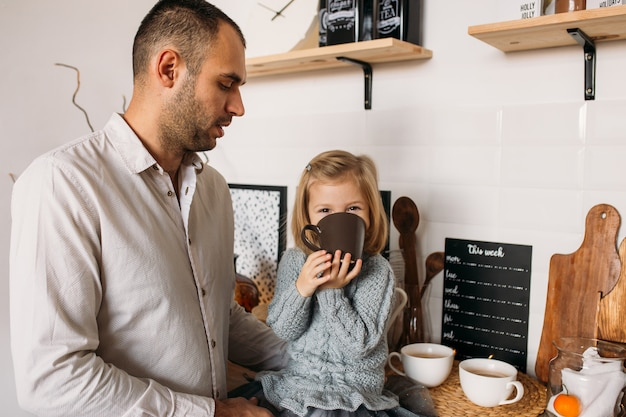 自宅のキッチンで彼女の父親と女の子。かわいい女の子はお茶を一杯とキッチンに座っています。