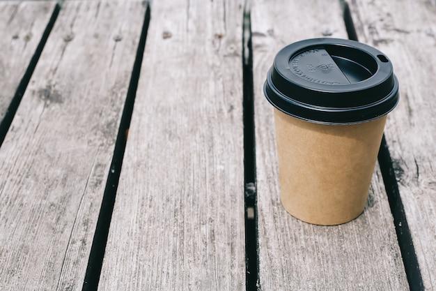 茶色の木製の背景にコーヒー紙コップ。コピースペース