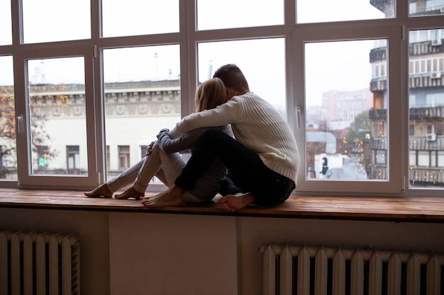 部屋の窓の近くに座っている幸せな若いカップル