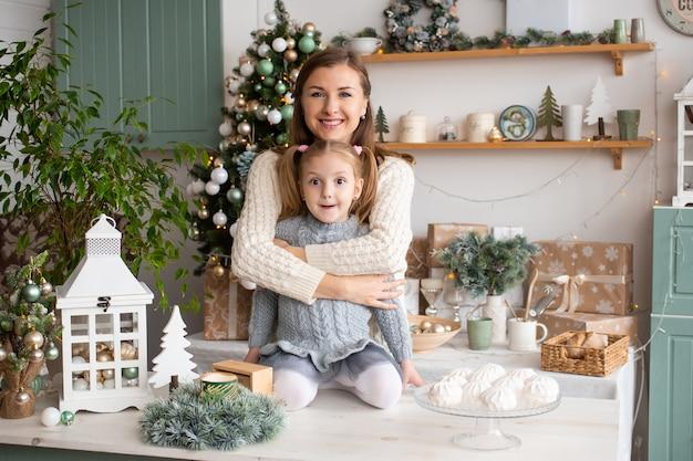 母は自宅のクリスマスキッチンで彼女の小さな女の子を抱き締めます。