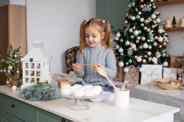 かわいい面白い女の子はクリスマスの家で台所のテーブルに座っています。