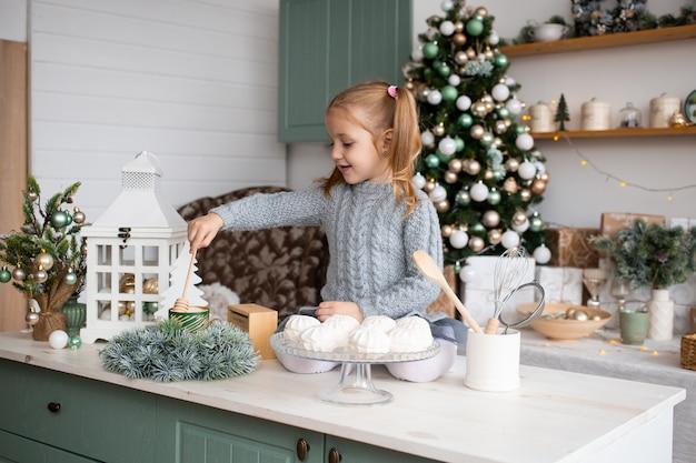 女の子はクリスマスの家で台所のテーブルに座っています。