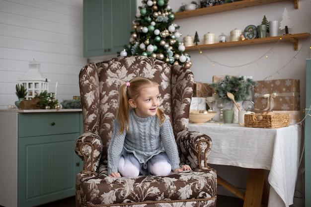 Забавный ребенок сидит в кресле в доме рождества