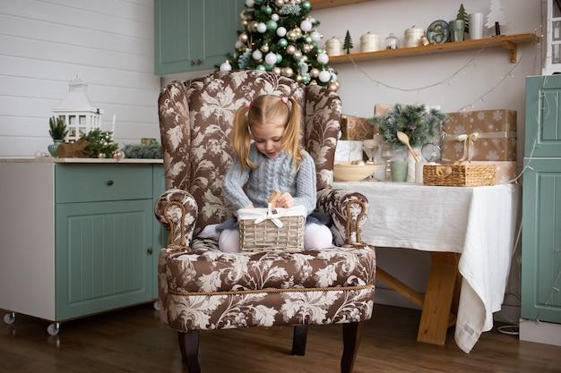 Маленькая девочка сидит в кресле на рождество дома