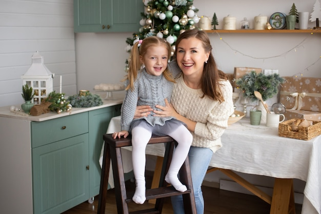 娘と母のクリスマスの背景に笑みを浮かべて