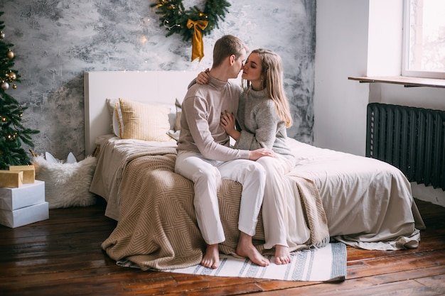 クリスマスの時に自宅のベッドで若いカップル