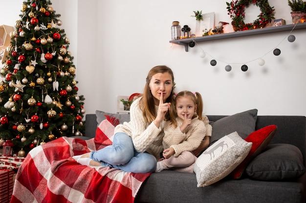 母と少女は自宅でクリスマスイブにクリスマスツリーの近くで遊んでリラックスします。