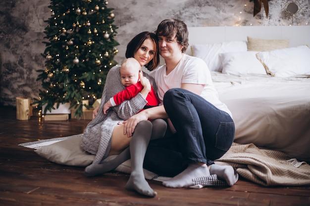 家族と自宅のクリスマスツリーのそばに座って赤ちゃん