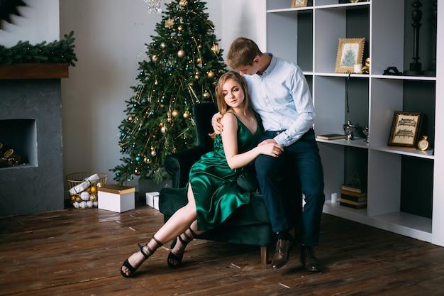 Влюбленная пара проводит время возле елки, новый год