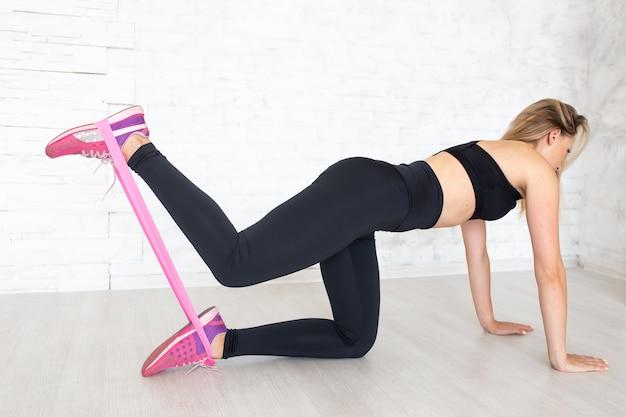 床にゴムバンドで運動をしている女性