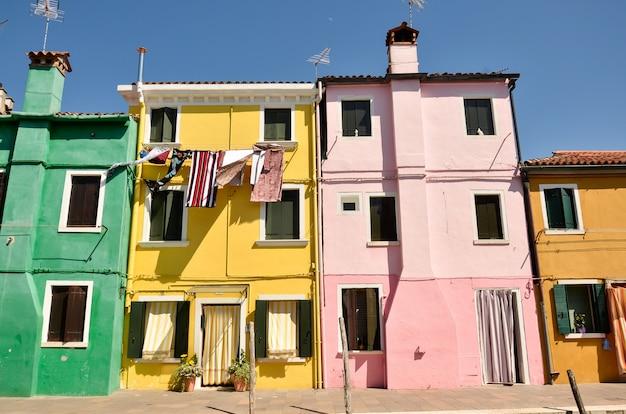 Дома в бурано, венеция, италия. красочная концепция, желтый, розовый и синий