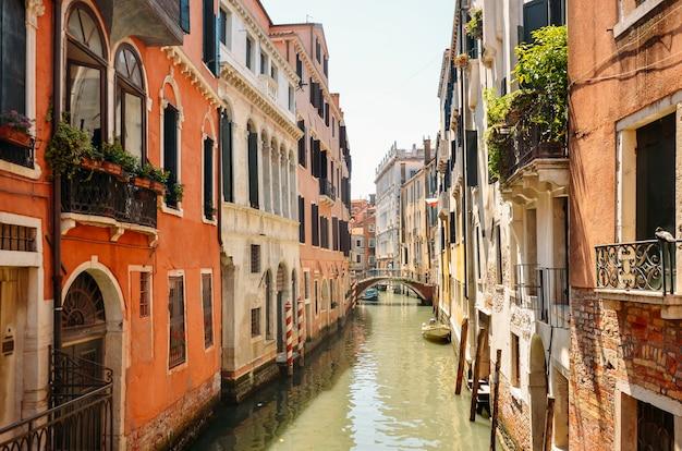 Узкий канал с шлюпкой и мостом в венеции, италии. архитектура и достопримечательность венеции. уютный городской пейзаж венеции