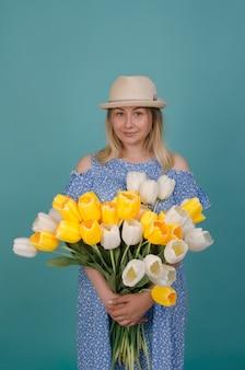 花を持つ若いブロンドの女性の肖像画。青いドレスで彼女の手に花の束を持つ女性の笑みを浮かべてください。夏と春のコンセプト