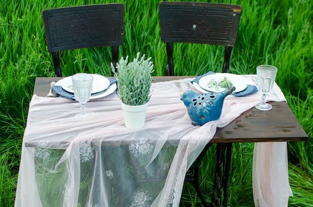 Таблица украшения свадьбы в деревенском стиле на зеленой траве. закройте темный деревянный стол, белая скатерть, посуда и хрустальные бокалы. горшок с зелеными цветами и украшения с старинные птицы.