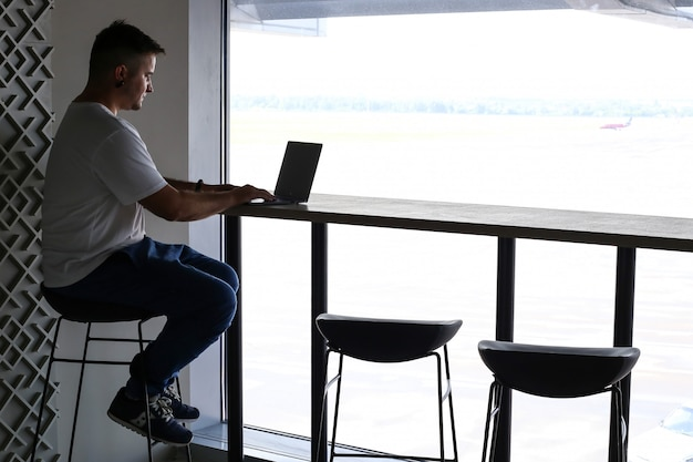 コンピューターのラップトップに取り組んでいるとコーヒーを飲むと創造的なフリーランサー男