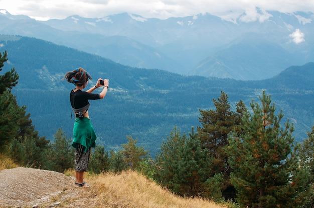 女性は山の写真を撮る