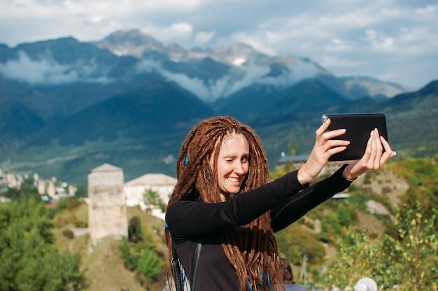 Битник путешествия женщина с дредами, делая селфи с ее смартфон