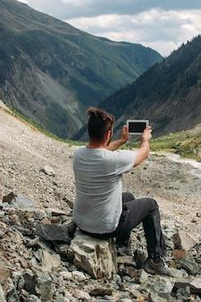 旅行者は山で彼のタブレットで写真を作ります