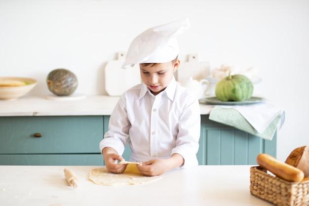Ребенок в шляпе шеф-повара дома печет печенье на кухне