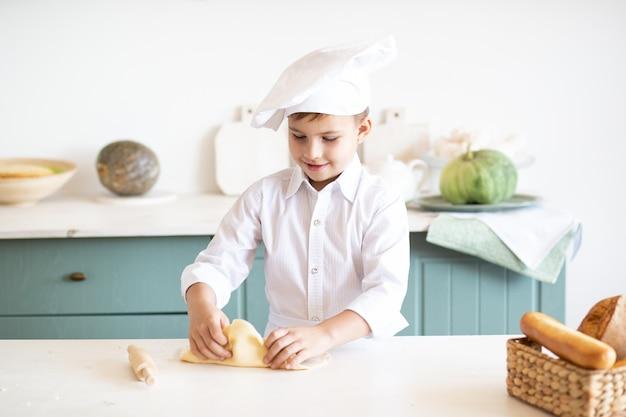 Маленький ребенок в шляпе шеф-повара дома печет печенье на кухне