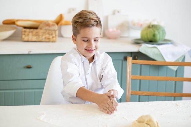 国内キッチンでクッキーを焼く少年