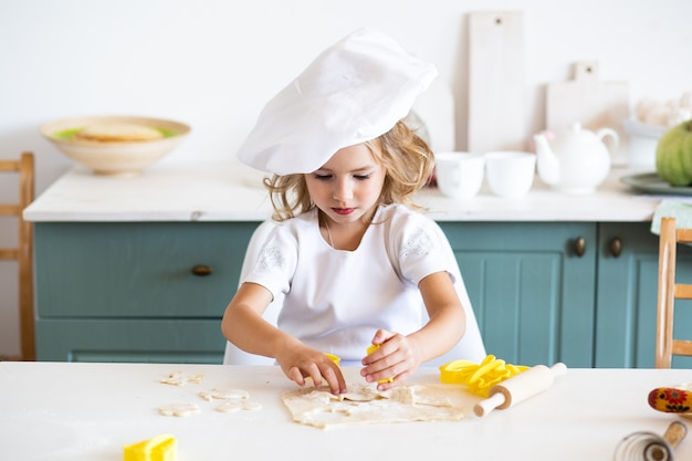 かわいい女の子がフォームとキッチンでクッキーの生地をカットします。