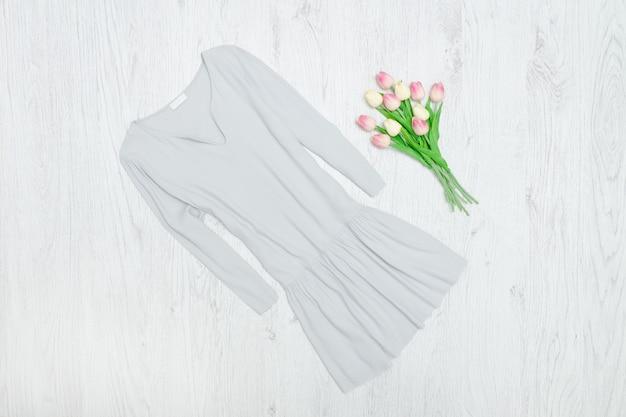 グレーのドレスとチューリップの花束。ファッショナブルなコンセプト