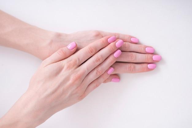 優しいピンクのマニキュア。白い背景の上の女性の手