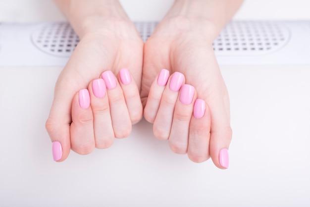 Нежный розовый маникюр. женские руки в маникюрном салоне