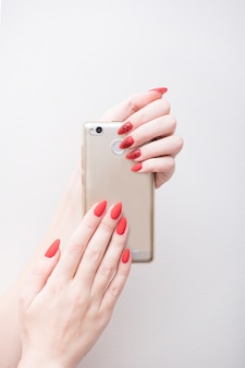 Красный маникюр с рисунком. смартфон в женской руке. белый фон