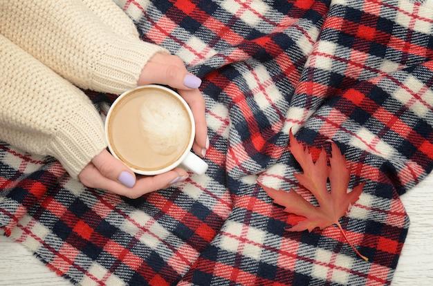 女性の手、格子縞の格子縞、秋の葉のカプチーノ