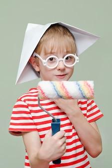 Мальчик в бумажной шапке и очках играет художника