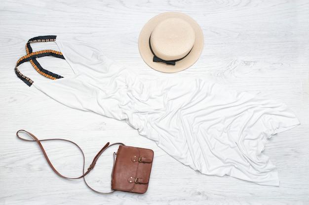 麦わら帽子、白いサンドレス、ハンドバッグ