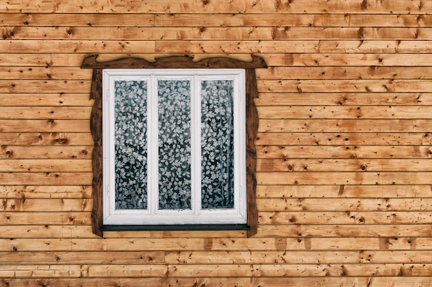 Белое деревянное окно в стене сырцовых коричневых деревянных планок с узлами.