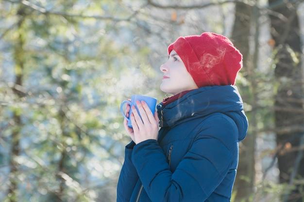 赤い帽子と彼の手の立っているマグカップの女の子